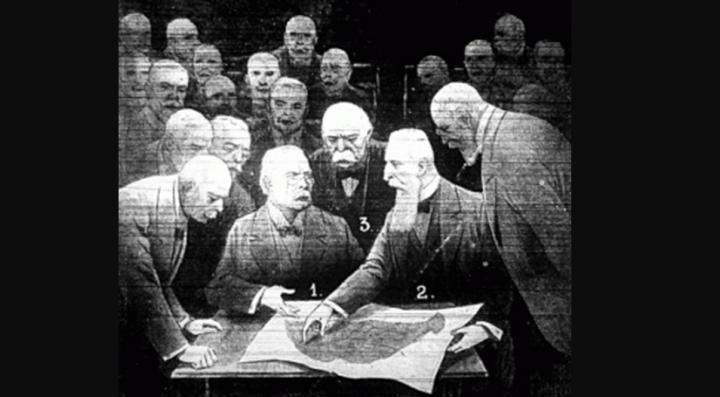 Hatalmasságok a Magyar királyság térképe fölött. Az asztalnál ülnek Lloyd George és Apponyi föléjük hajol középen Clemenceau