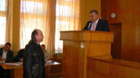 """Riskó György, a """"KMKSZ""""-UMP képviselője átnyújtja Mihajlo Ljaskónak a bátyúiak beadványát. A háttérben Heé Roland a """"KMKSZ""""-UMP frakcióvezetője"""
