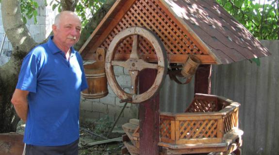 Fekete József otthona udvarán, egyik munkája mellett