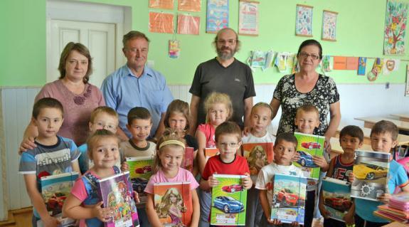 A képen balról jobbra: Jakab Anikó, az első osztály tanítónője, Balog Zoltán, a KMKSZ helyi alapszervezetének elnöke, Balázsi Csaba, a KMPSZ badalói képviselője, és Sverga Margit iskolaigazgató és a boldog elsősök.