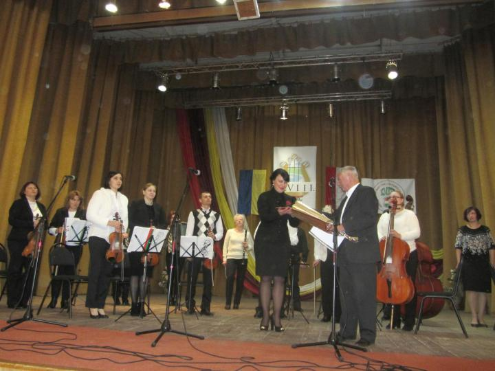 Sari József virágot és emléklapot nyújt át a Técsői Járási Művészeti Iskolák Népi Zenekara vezetőjének