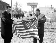 A Nagy Sándor (balról) és Illár József (jobbról) kibontják az amerikai lobogót a határon