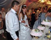 Az ifjú pár felvágja a menyasszonyi tortát